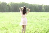 Girl in a dress jumping in a field — Stock Photo