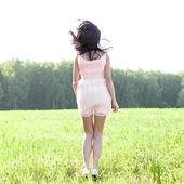 Mädchen in einem kleid in einem feld springen — Stockfoto