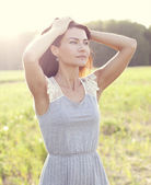 Woman in a dress standing in a field — Stock Photo