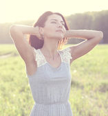 Girl in a dress standing in a field — Stock Photo