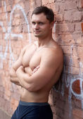 Young bodybuilder near brick wall — Stock Photo
