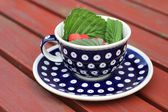 A cup from polish pottery in Bunzlau with raspberries — Stock Photo