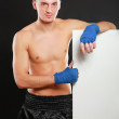Young handsome boxer man standing near board , isolated on black background — Stock Photo #47573181