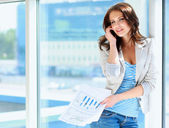 Portrait of young businesswoman talking on mobile phone on office hallway. — Stock Photo