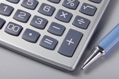Pen and calculator on business paper — Stock Photo