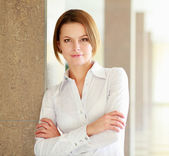 Portrait of young busineswoman standing in office lobby. — Stock Photo