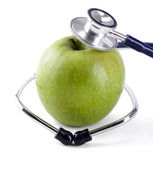 Stethoscope and green apple isolated on white background — Stock Photo