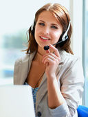 Businesswoman talking on the phone while working on her computer at the office — Stock Photo