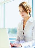 Happy businesswoman working on laptop — Stock Photo