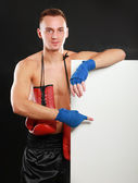 Young handsome boxer man standing near board , isolated on black background — Foto de Stock