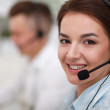 Businesswoman with headset smiling at camera in call center — Stock Photo #51208691