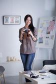 Mujer es un fotógrafo profesional con cámara en oficina — Foto de Stock