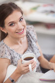 Woman sitting on the couch with a cup in her hands — Stock Photo