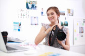 Young woman photographer processing pictures sitting on the desk — Stockfoto