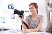 Young woman photographer processing pictures sitting on the desk — Foto de Stock