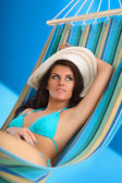 Woman relaxing on hammock with white hat — Stock Photo