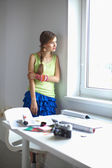 Portrait of a young beautiful photographer woman  on the table. — Stock Photo