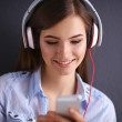 Smiling girl with headphones isolated on grey background — Stock Photo