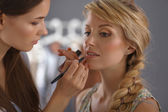 Artist doing professional make up of woman — Stock Photo