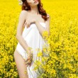 Young attractive sexy girl on a sunny day of flowering rape field with flowers in red hair — Stock Photo #47218155