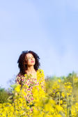 Happy carefree young beautiful girl basking in the sun in the field — Stock Photo