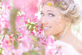 Young beautiful elegant, attractive girl standing in a forest near flowering tree with long hair blond in Sunny day and makeup among flowers with blue eyes — Zdjęcie stockowe