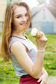 Young beautiful happy girl on a Sunny day walking around the city and eat ice cream — Stock Photo