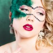 The beautiful young woman in a green mysterious venetian mask a new year carnival, Christmas masquerade, a dance club, secret night party, with beautiful makeup — Stock Photo #48727877
