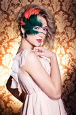 The beautiful young woman in a green mysterious venetian mask a new year carnival, Christmas masquerade, a dance club, secret night party, with beautiful makeup — Stockfoto