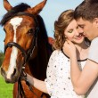 Loving beautiful couple of guys and girls in the field walk on horses — Stock Photo #48735031