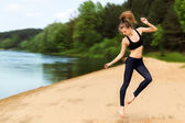 Young energetic girl who is engaged in fitness on the beach near the river — Stock Photo