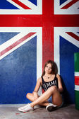 Beautiful young girl in jeans shorts sports shoes sits near the barrels in the Studio on the background of the flag of Britain — Stock Photo