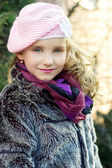 Little beautiful girl with blue eyes in pink hat standing on the street — Stock Photo