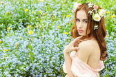 Beautiful sexy young girl with long red hair with flowers in her hair, sitting in a field in blue flowers — Stock Photo