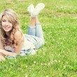 Happy young beautiful sexy girl lying on the grass and smiles in jeans in a Sunny summer day in the garden — Stock Photo #49846199