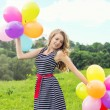Beautiful young blonde girl smiles on a summer day walks with colored balls in the city — Stock Photo #49848213