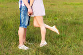 Young happy couple kissing in love, standing on the grass in the summer sun the night — Stock Photo