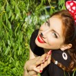 Beautiful girl happy smiling in the costume of a mouse with a big red bow down on the grass in the Park — Stock Photo #50262719