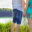 Beautiful young happy couple is standing on the Bank of oneoa on a Sunny day, a girl in a blue dress and the guy in jeans — Stock Photo #50482023
