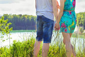 Beautiful young happy couple is standing on the Bank of oneoa on a Sunny day, a girl in a blue dress and the guy in jeans — Stock Photo