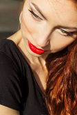 Beautiful sexy girl with red hair with big red lips with makeup in the city on a Sunny summer day — Stock Photo
