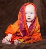 Baby girl wrapped in an orange scarf — Stock Photo