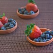 Strawberries and blueberries in small clay dishes on a mat — Stock Photo #48456821
