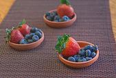Morangos e mirtilos em pratos de barro em uma esteira — Fotografia Stock