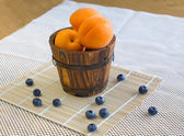 Ripe apricots in a bucket and blueberries on white — Stock Photo