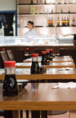 Bottles of soy sauce on the tables in a sushi restaurant — Stock Photo