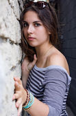 Girl in striped shirt by stone wall — Stock fotografie