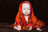 Baby wrapped in red orange scarf — Stock Photo