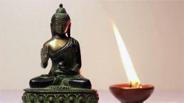 Statue von buddha und eine brennende kerze. — Stockvideo