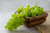 Bunch of grapes in a wooden bowl — Stock Photo